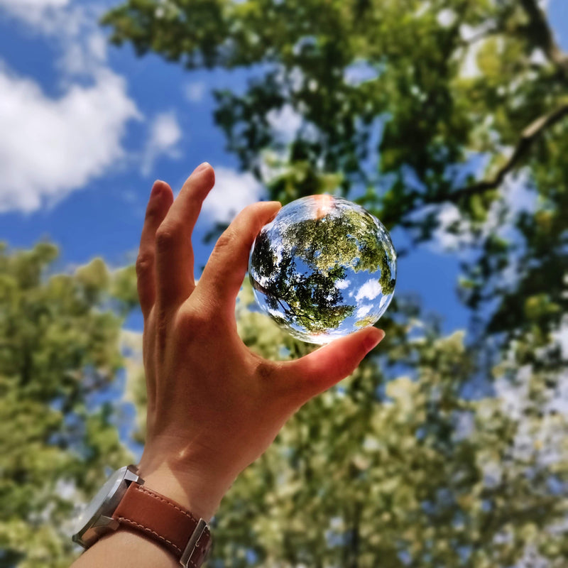 Holding a glass sphere in front of green trees and a blue sky