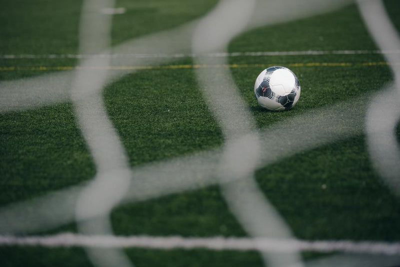 Soccer ball on a field seen through a goal net
