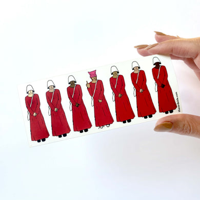 Line of seven handmaids, all with different skin colors, one handmaid in the center holds up her middle finger, she's wearing a pink pussy hat and untied Converse-style shoes