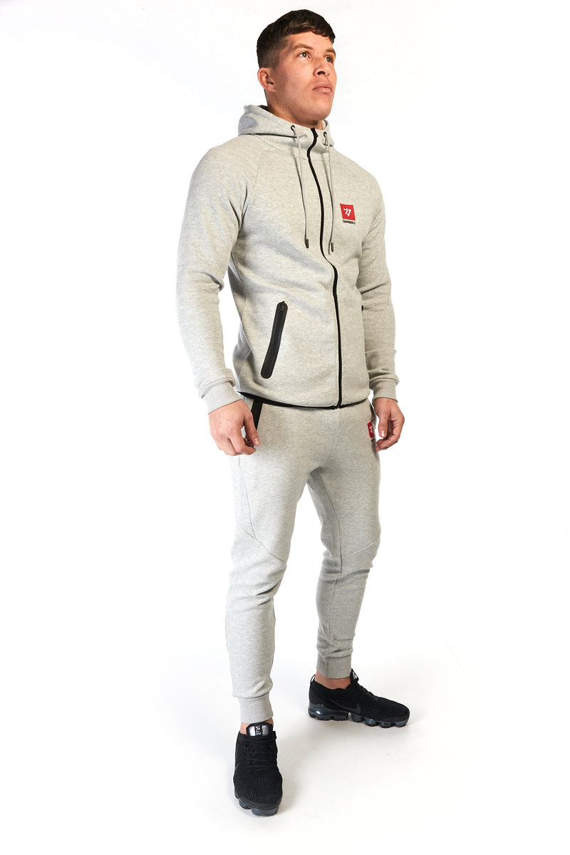 Man wearing grey, slim fit tracksuit pants with red logo on the left thigh