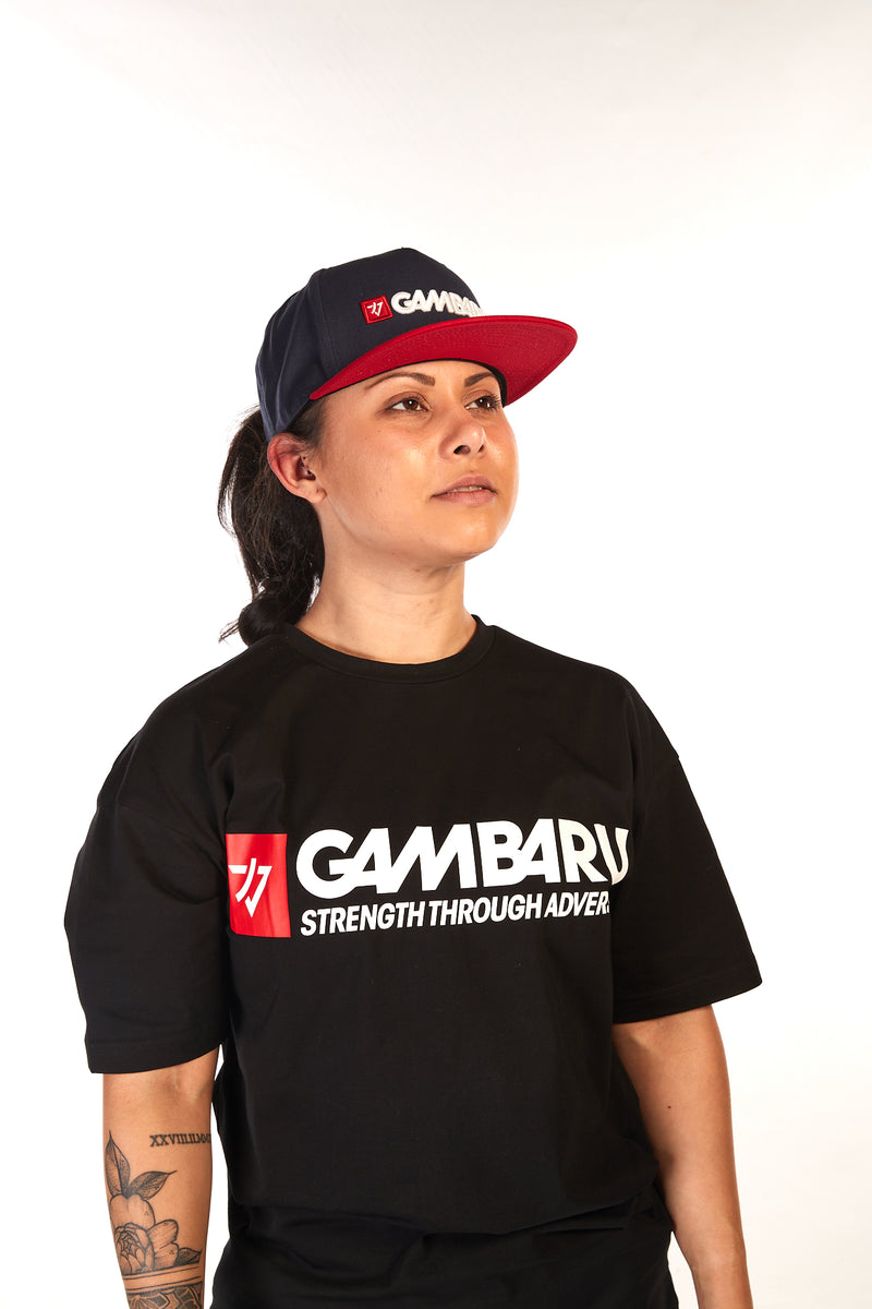 Woman wearing navy blue hat with a flat, red peak and Gambaru Fightwear logo on the front