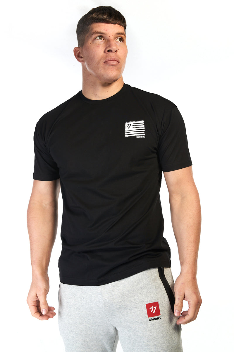 Man wearing unisex black cotton tshirt with small white flag style logo on the chest and big flag logo on the back