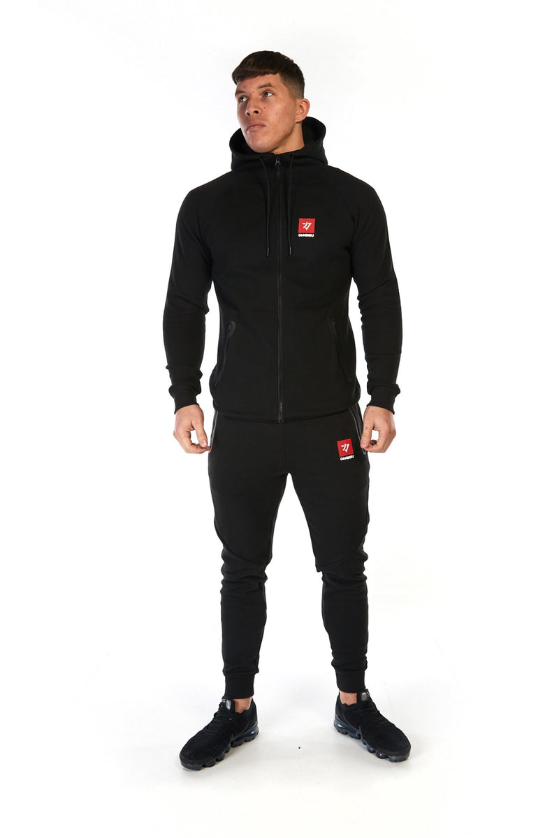 Man wearing unisex black cotton hoodie (hoody) in a slim fit with full zip and red logo on the chest