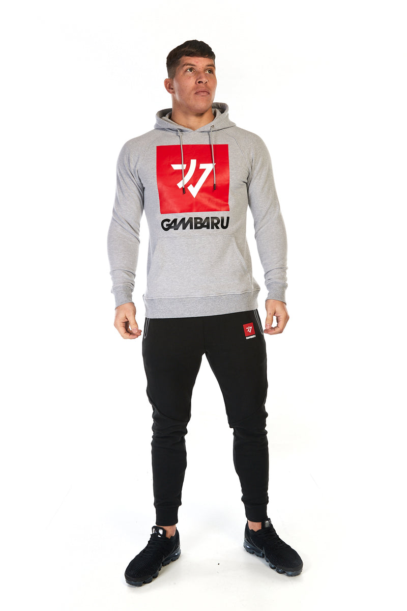 Man wearing grey cotton unisex hoodie (hoody) with big red Gambaru Fightwear logo on the front