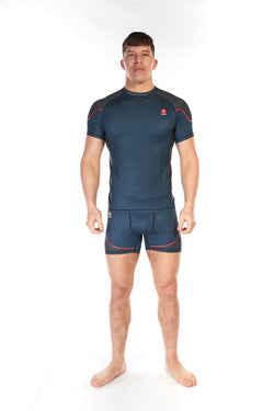 Man wearing short sleeve mid-blue unisex training top with piping across the upper shoulders
