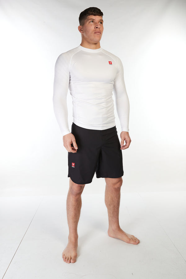 Man wearing unisex long sleeve training top in white with small red Gambaru Fightwear logo on the chest