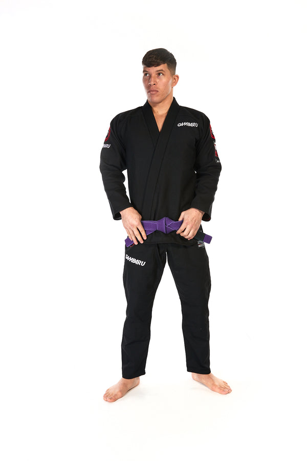 Man wearing unisex fightwear gear in black with white Gambaru Fightwear logo on chest and right thigh