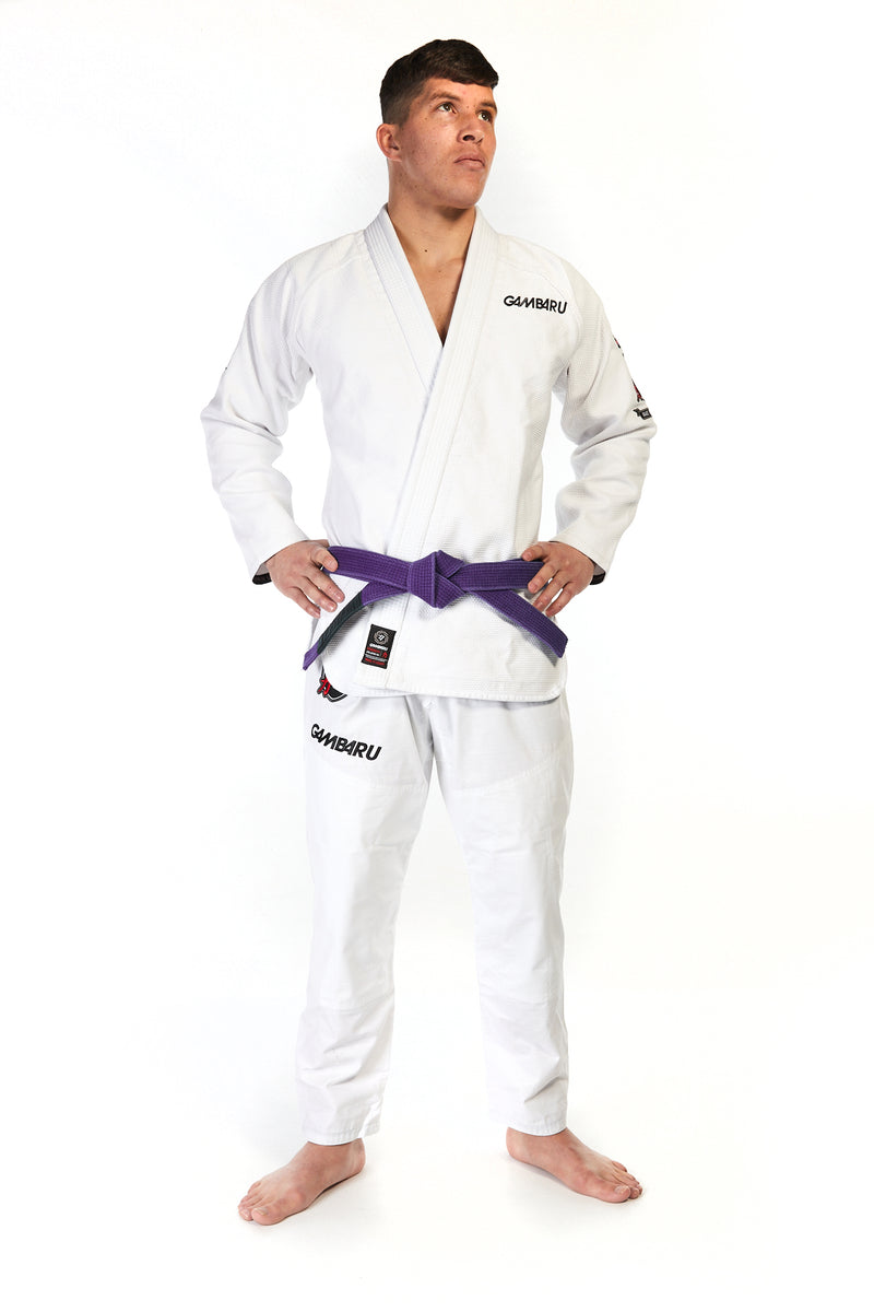 Man wearing unisex fightwear gear in white with black Gambaru Fightwear logo on chest and right thigh