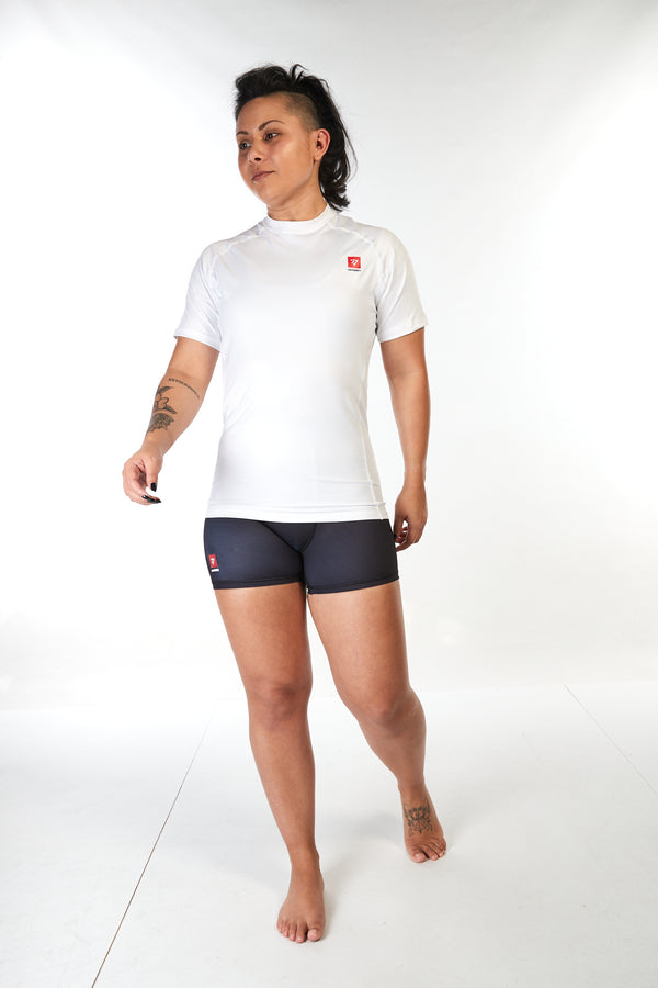 Woman wearing unisex short sleeve training top in white with small red Gambaru Fightwear logo on the chest
