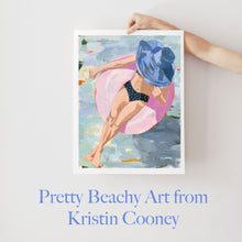 Load image into Gallery viewer, Kristin Cooney's fine art giclee print of a pretty woman in a bikini floating in an innertube in a beautiful water scene, has a feminine palm beach vibe and is the perfect art to add some fun and elegance any home decor, interior design. Printed on Archival Matte Paper Metallic Bamboo frame or natural wood frame.