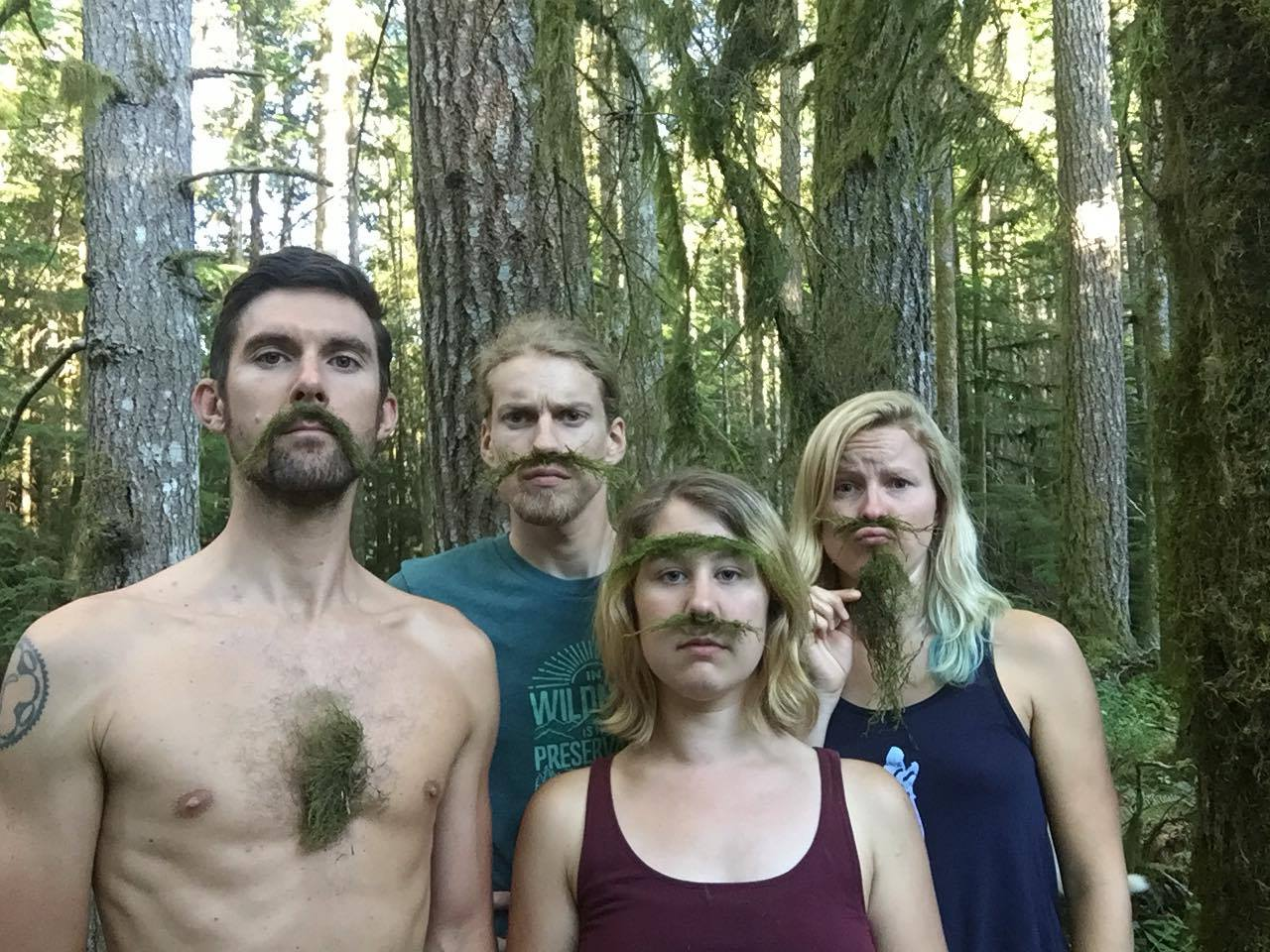 the we are wildness team making funny faces in the forest with old man's beard that we found blown onto the ground
