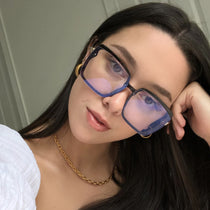 brunette wearing the 016 black and blue light glasses