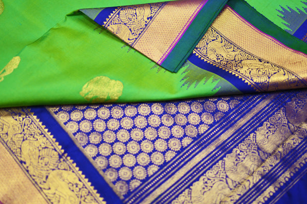 Kanchi pure silk saree in green with elephant motifs and a temple border.