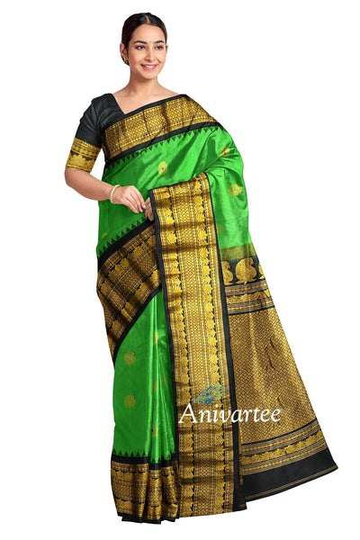 Gorgeous Handloom Gadwal pure silk saree in green with elephant & disc motifs in meena and a 9 inch large kuttu temple border.