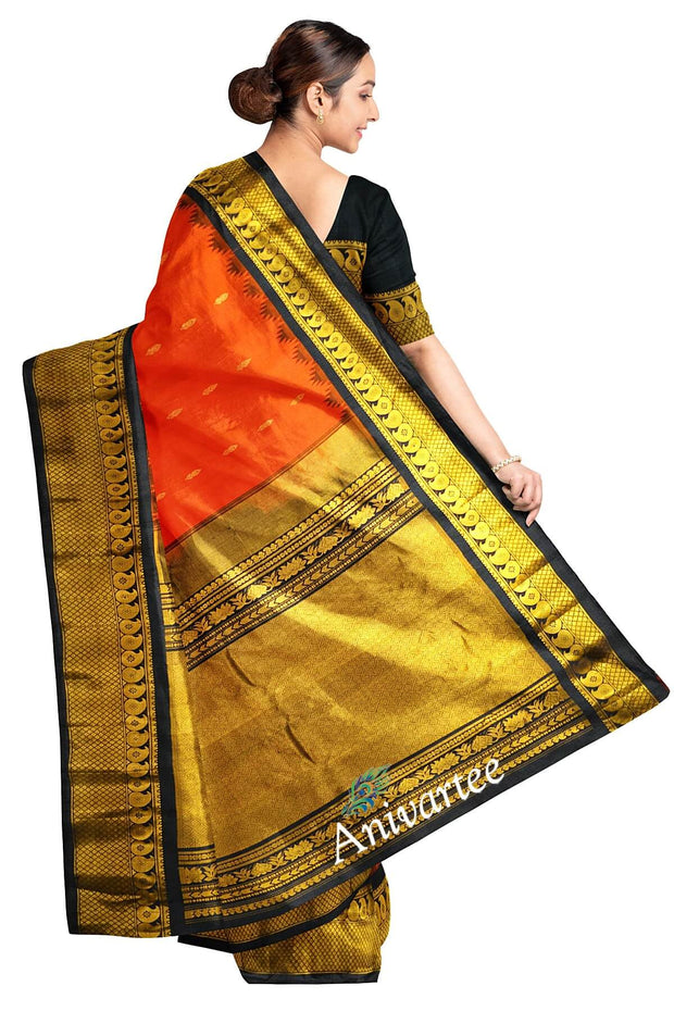 Handloom Gadwal pure silk saree in orange  with floral motifs  and a 8 inch large kuttu  temple border.