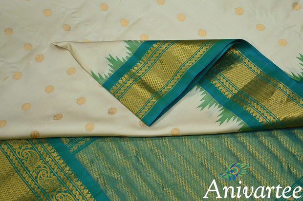 Handwoven Gadwal pure silk saree in off white with round  motifs and  and a large kuttu temple border in teal green