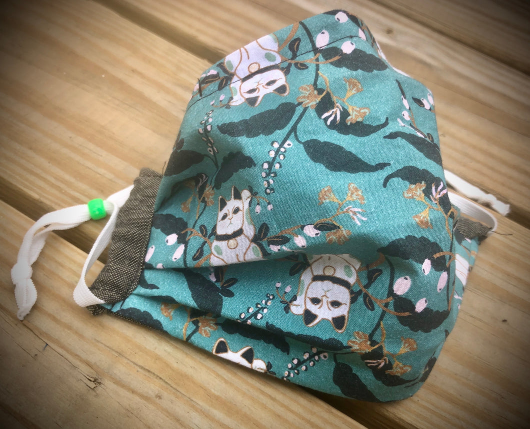 Teal waving cats face covering with pocket for filter