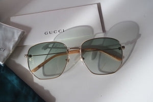 Gucci 0396S Gold Oversized Round Logo Sunglasses in Green