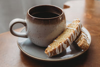 2 lemon drizzle biscotti on the saucer of a cup of coffee
