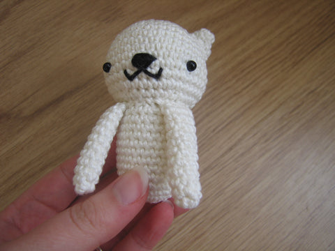 Sitting cat with front legs sewn to the body