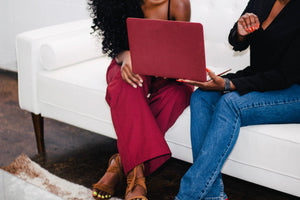 two black women sitting on a white couch. one is wearing a black tank top and burgundy pants, holding a burgundy laptop. The other is wearing a black long-sleeve shirt and blue jeans