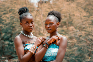 two black women standing in front of a nature backdrop both wearing traditonal african pattern tube top drresses