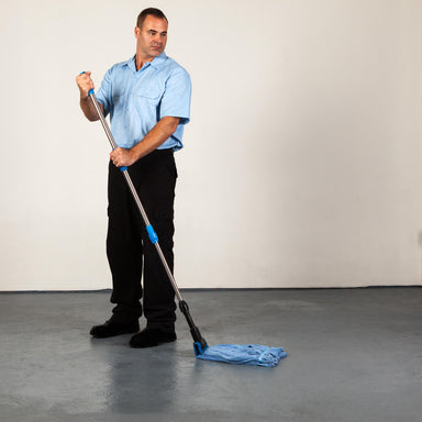 Janitor using rough floor mop on concrete