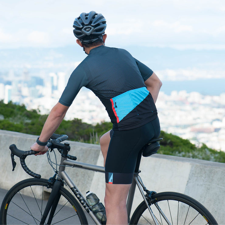Male modeling wearing black bib shorts while on bike.