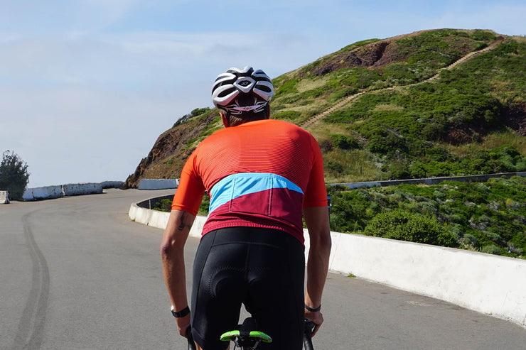 Red, maroon and blue, striped cycling jersey on a male model.