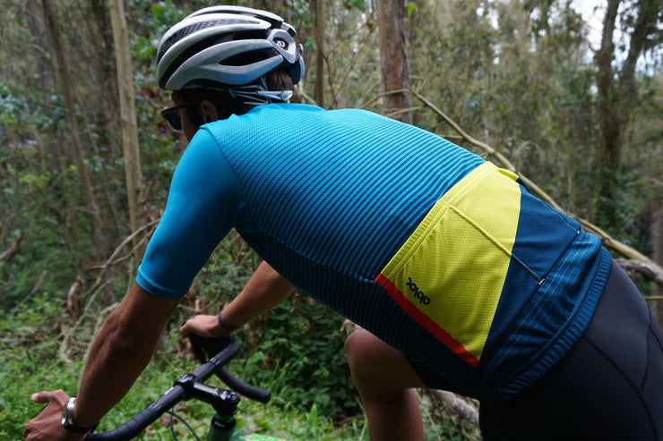 Light blue, teal and yellow, striped cycling jersey on a male model.
