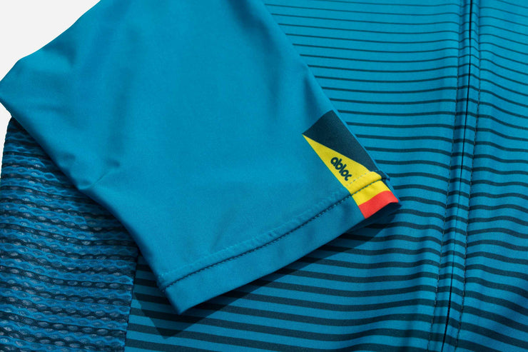 Light blue, teal and yellow, striped cycling jersey on a table.