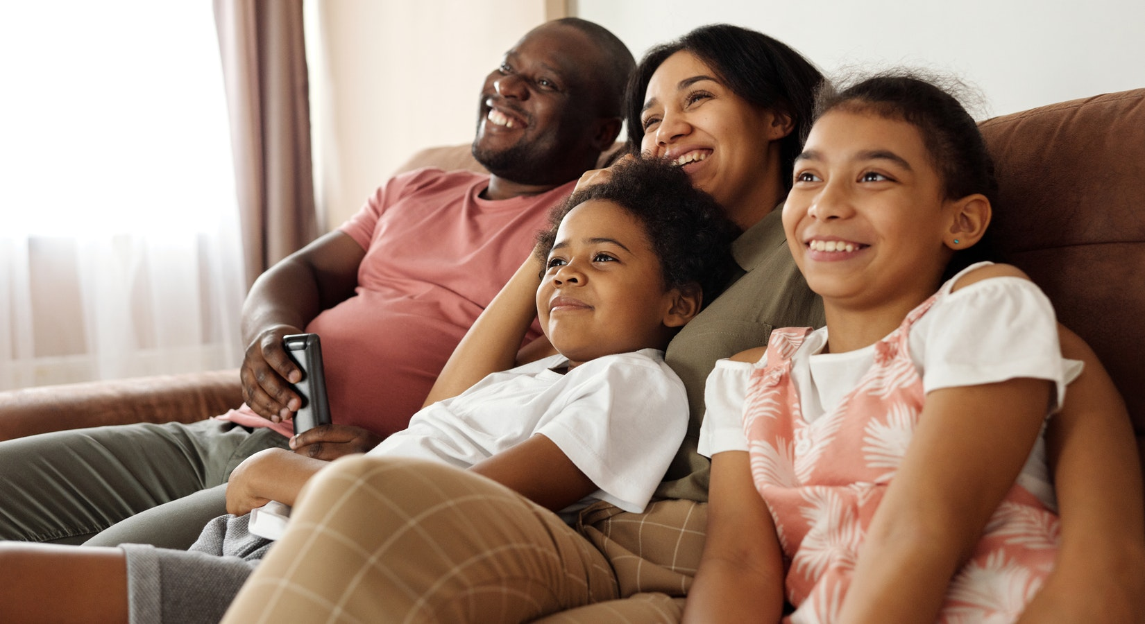 Happy family sitting on a couch and watching tv