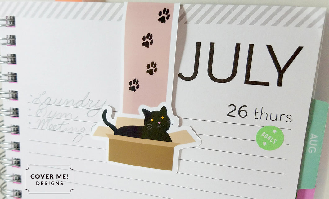 black cat in a cardboard box with paw prints magnetic bookmark on planner