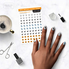 Load image into Gallery viewer, happy halloween nail decals with pumpkins, black cats, bats, skulls, and ghosts on table