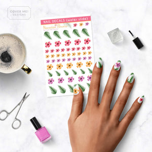 hawaiian flower nail decals with hibiscus flowers and palm leaves on table