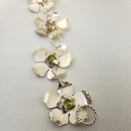 Yamka collection; sterling silver 7-flower hibiscus bracelet with peridot gemstones.