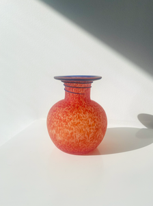 Red speckled art glass vase with purple design