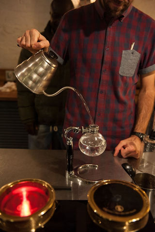 Mike pouring water into bottom chamber of siphon using Hario kettle