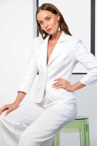 Seated model wearing Kamare Collective Thurlow Jacket in White Linen.