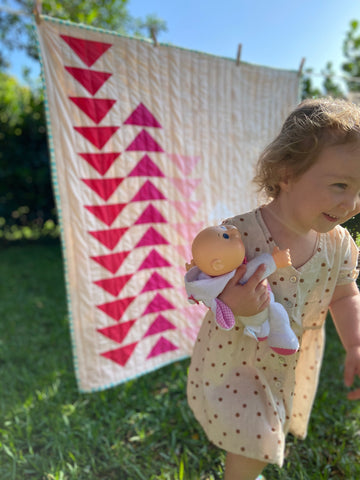 toddler girl running in front of quilt with toy