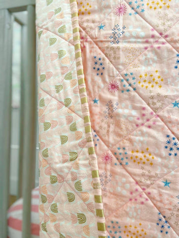 pink and gold binding fabric on rainbow quilt