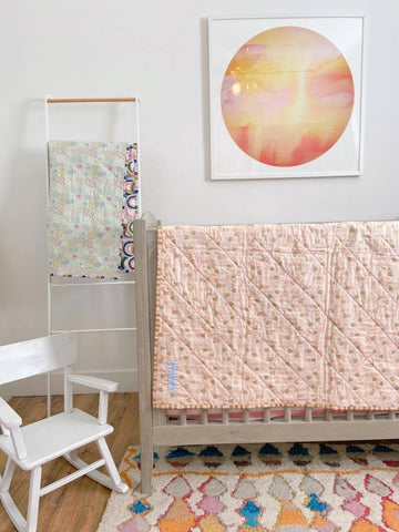 rainbow quilts hanging on crib and blanket ladder in nursery