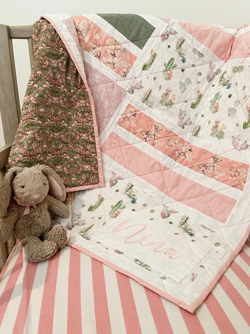 baby quilt hanging in crib with stuffed bunny