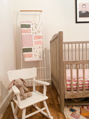 pink and green baby girl quilt in nursery