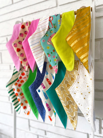 baby bibs hanging on ladder in front of white wall