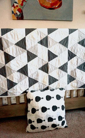 grey triangle quilt in a nursery