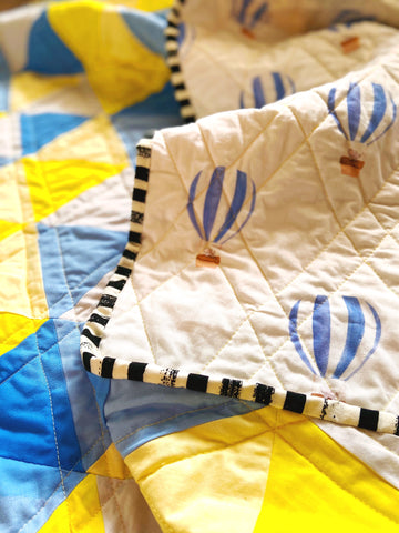 black and white striped fabric binding on baby quilt