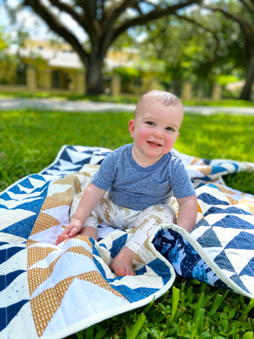baby boy sitting on his polar bear quilt outside