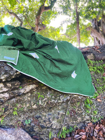 custom king sized green quilt sitting on a rock