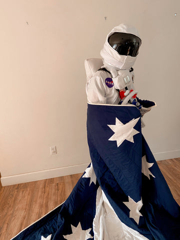man in astronaut costume wrapped in custom kid's rocket ship quilt